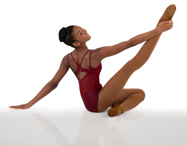 Dancer with plum-colored leotard and matching brown skin tone tights and dance slippers.