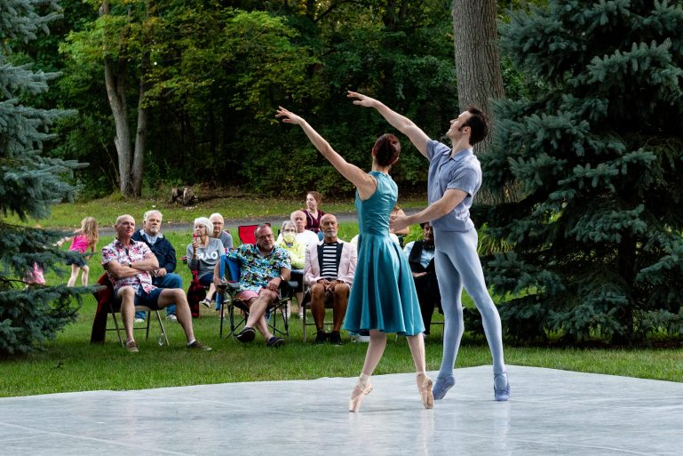 Two dancers—a man and woman—dance on a makeshift stage set up in a grassy backyard, as a group of patrons in lawn chairs look on