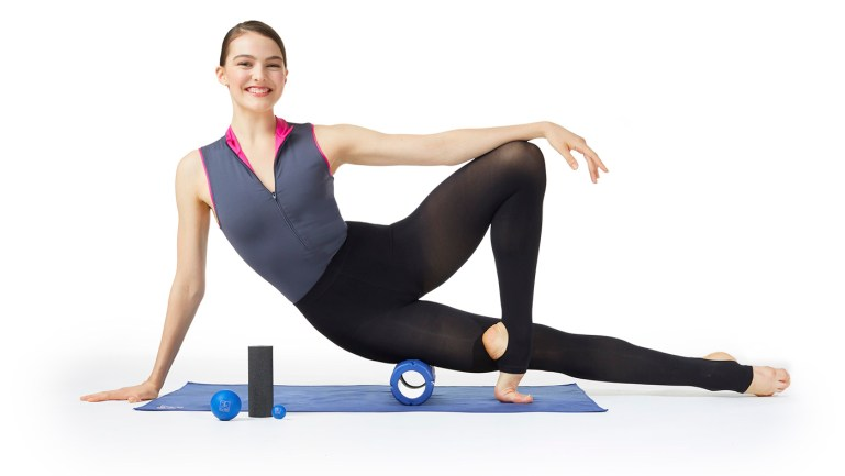 Dancer in sleeveless gray leotard with pink trim and black leggings balancing on blue foam roller