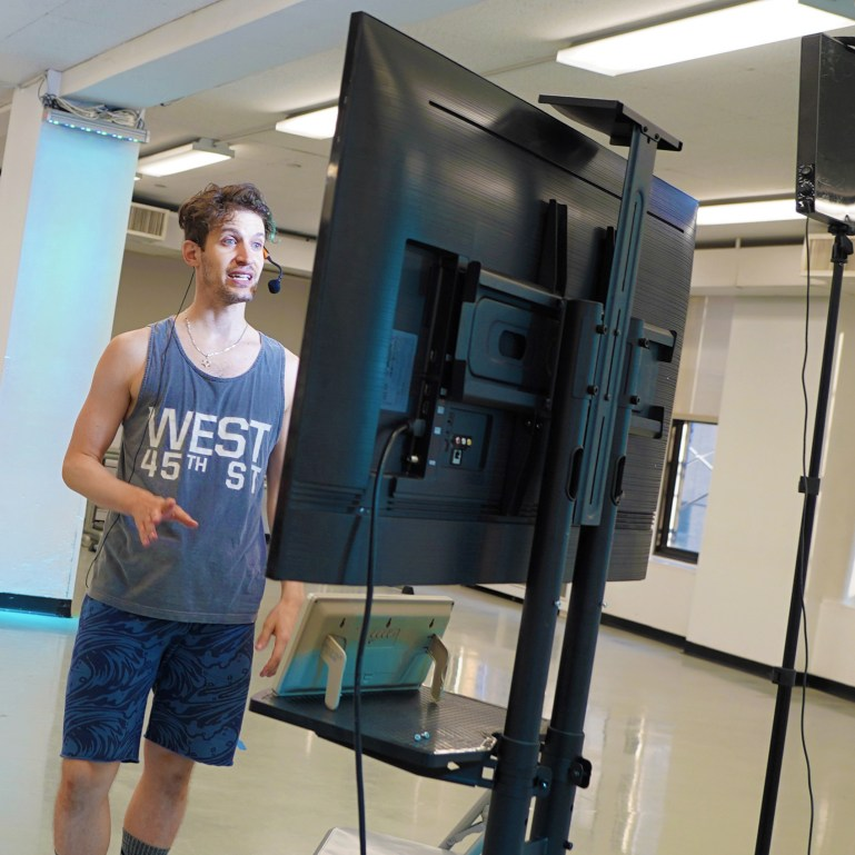 Barry Kerollis, a young white man with a streak of blue dyed in his brown hair, stands in front of a large monitor in an empty dance studio, talking into a microphone.