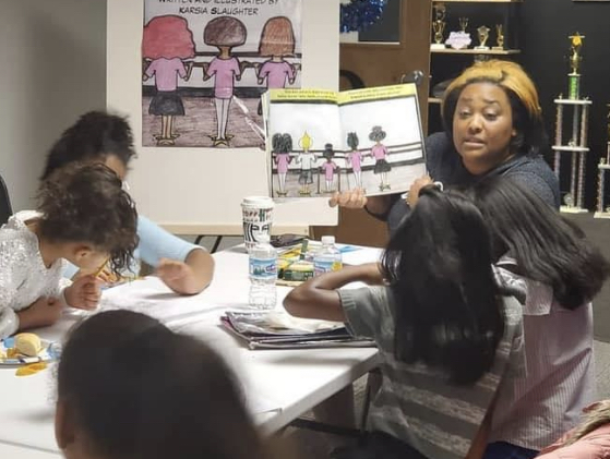 Woman at end of table holding up a picture book with an illustration of dancers at a barre. Young girls are listening to the story.