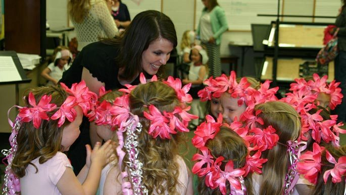 Bri Nelson, a middle-aged brunette, leans over a group of young girls who wear flower crowds. They gather around her, smiling.
