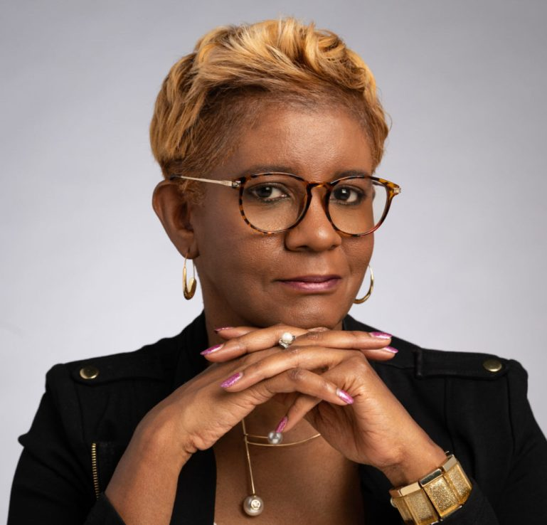 Portrait of Roshawn Buxton, owner of dance store, wearing glasses with hands clasped in front of her.