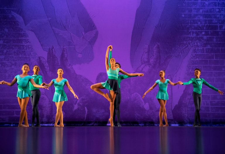Seven middle school aged students, all Black, perform a ballet piece onstage in front of a purple backdrop. They wear teal and black costumes.