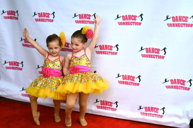 Two preschool-aged girls in sparkly yellow and pink costumes pose together on a red carpet. A backdrop with the Dance Connection logo is behind them