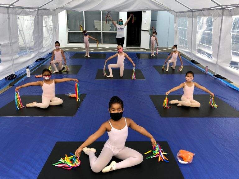 Nine young dancers and a teacher pose inside a tent in a parking lot. They hold rainbow ribbons and wear masks.