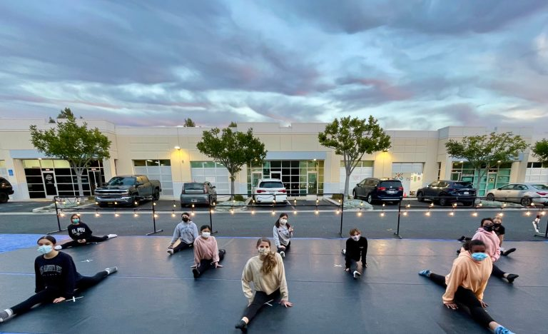 A group of teenage girls, all wearing masks, are in the splits on an outdoor stage in a parking lot. It is lit by fairy lights, and there is a business complex and some dramatic clouds behind them.