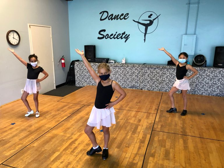 Three young dance students in masks pose in their dance studio, which has the Dance Society logo on the blue wall behind them.