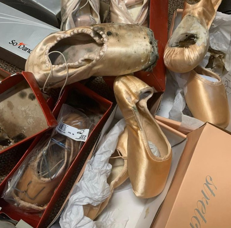 A pile of pointe shoes with mold damage
