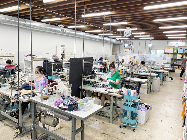 A large room with lots of tables and sewing equipment. Women in masks sit at the tables, hard at work.