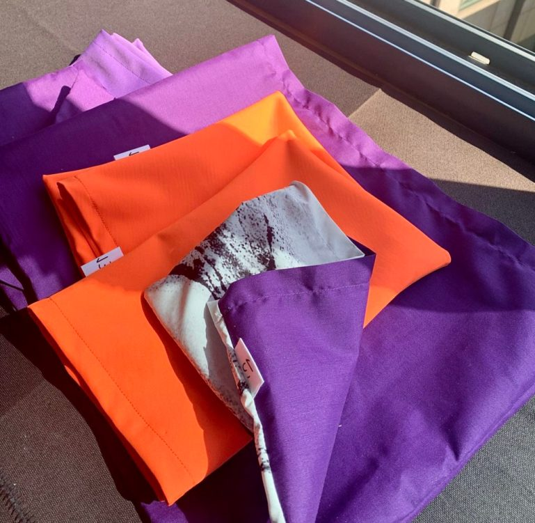 A pile of small orange and purple reusable bags lay on a table.