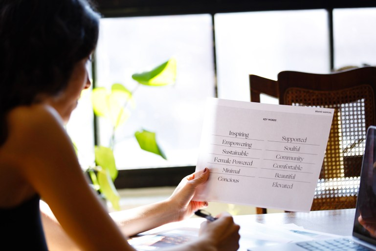 """Maya Kazzaz sits at a table, working. She holds a piece of paper containing """"key words"""" like Inspiring, Empowering, and Sustainable."""