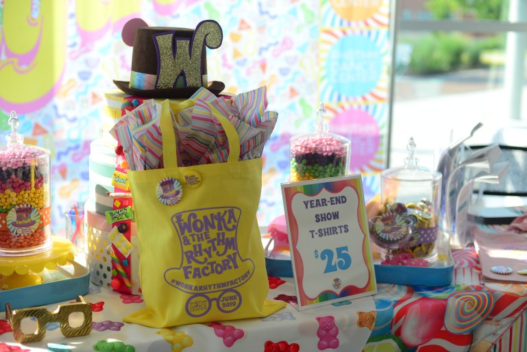 """A table with a colorful tablecloth and decorated with colorful candy has a bright yellow tote bag that says """"Wonka and the Rhythm Factory"""" and a sign advertising year-end show shirts for $25."""