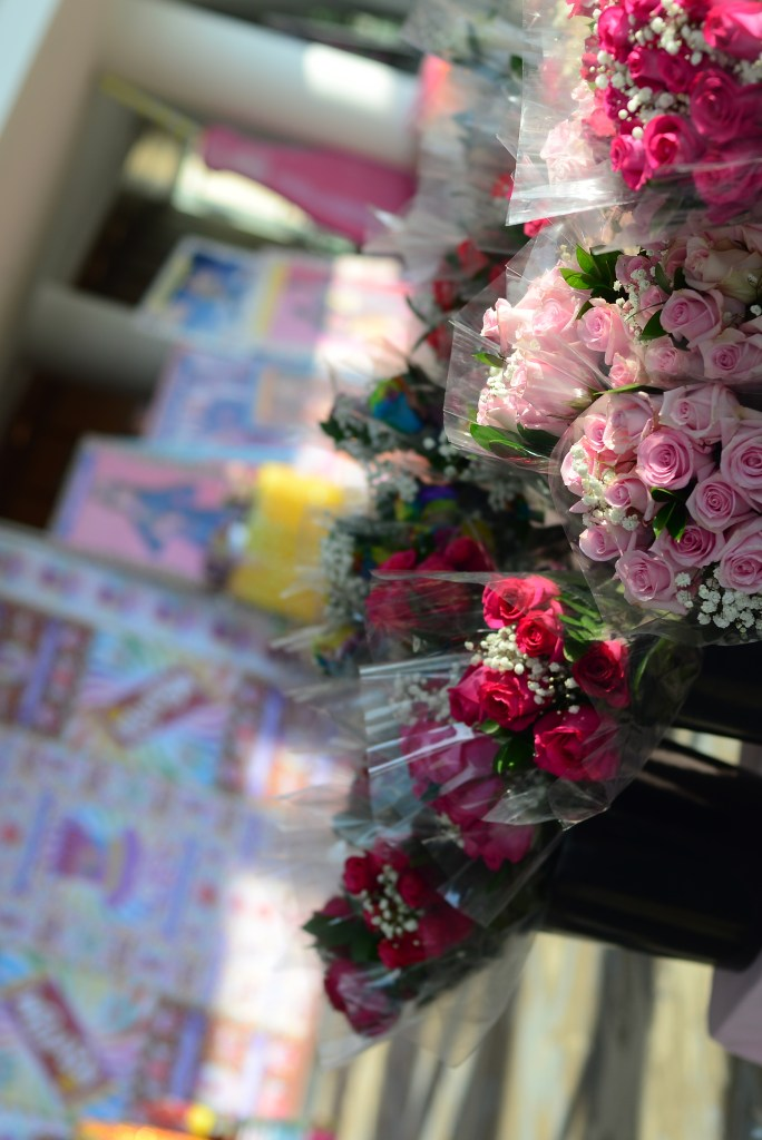 Buckets containing bouquets of flowers—mostly red and pink roses—sit on a table with a colorful tablecloth