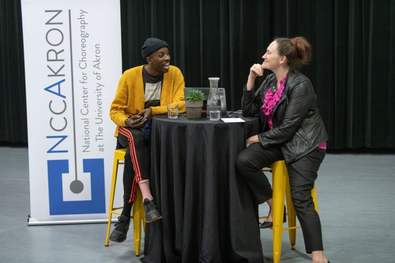 Christy Bolingbroke, in a leather jacket, and Raja Feather Kelly , in a yellow sweater, sit on either side of a high table draped in black fabric. A banner with NCCAkron's logo stands to Kelly's right. Bolingbroke and Kelly are talking animatedly. Kelly has his hands folded in his lap, and Bolingbroke has one hand under her chin.