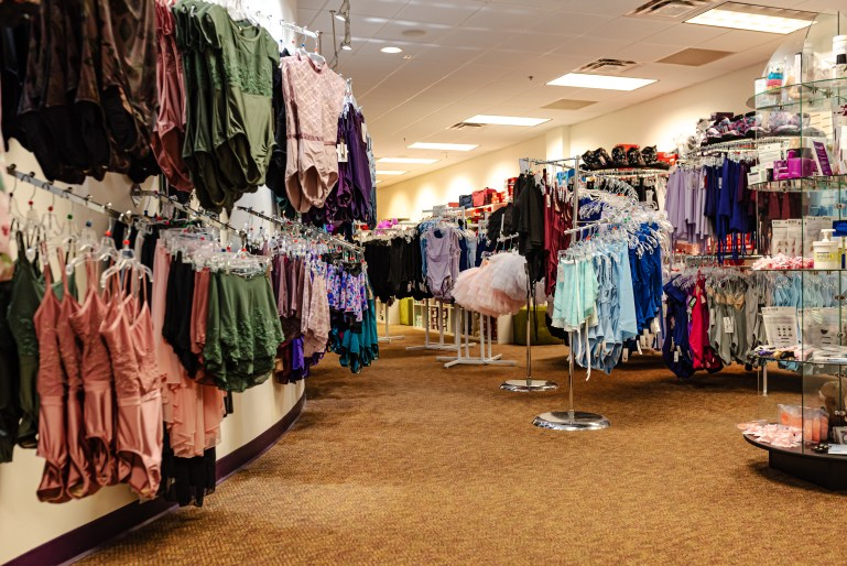 A small dancewear store has racks and displays full of colorful leotards and skirts, as well as shelves full of accessories.