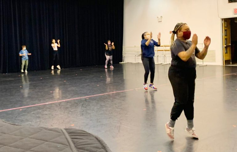 Four young students take a dance class from a teacher at the front of a large studio. Everyone wears masks and sneakers, and are clapping and jumping slightly off the floor.