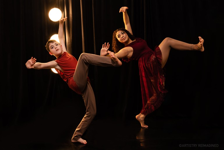 Two young dancers, a boy and a girl, strike the same pose: One leg in the air, knee bent and foot flexed, leaning slightly backwards and both arms extended, wrists flexed. They are lit from behind with a bright light