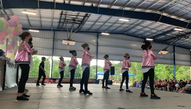 A group of young dancers perform a jazz dance on an outdoor stage, with the audience seated on camping chairs. The young women wear shiny pink jackets, the young man wears all black, and they all wear masks.
