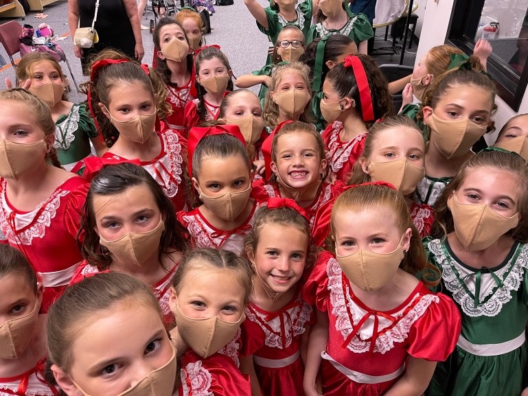 A large group of girls, some in red dresses and some in green dresses, and all wearing masks, gather to pose for a photo backstage.