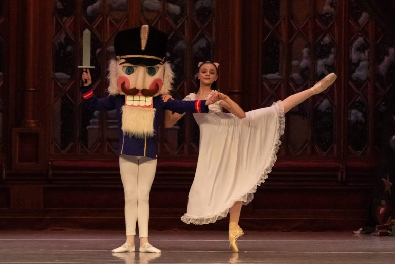 A young dancer plays Clara, in a long white nightgown-like dress, and partners with the Nutcracker, who wears a big Nutcracker head. Clara is in arabesque, holding onto her Nutcracker's arm for support.