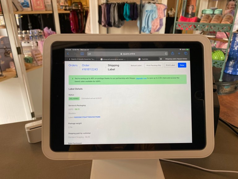 A photo from behind the counter at On Your Toes Performance Wear. A computer screen shows a page from Shippo's site, with tracking and shipping information about an order.