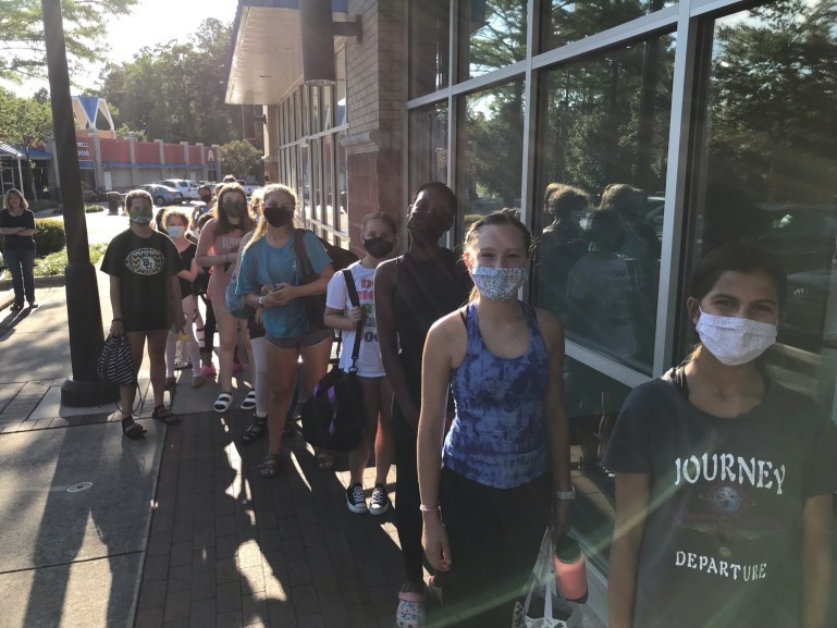 Teen stage door students line up outside the studio waiting to come in for class. They wear masks.