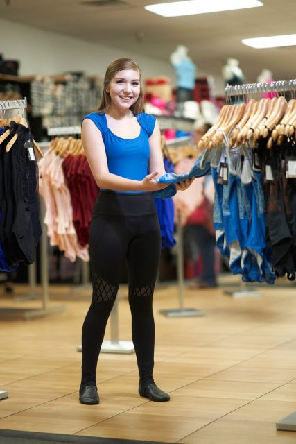 A young woman wearing a blue leotard, black pants and black jazz shoes smiles while holding a blue leotard hanging from a rack.