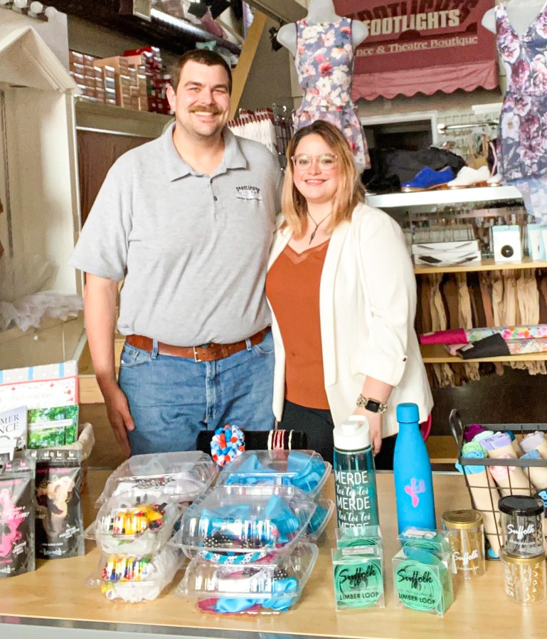 Molly Ellis stands with a man behind a table full of dance accessories like water bottles. Behind them is a Footlights sign as well as dance shoes, leotards and other store products.