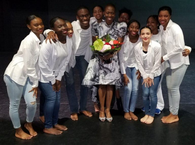 Dwana Smallwood wears a black and white dress and heels and holds a large bouquet of flowers. She is surrounded by teenage students, who wear jeans and white button-downs after a performance.