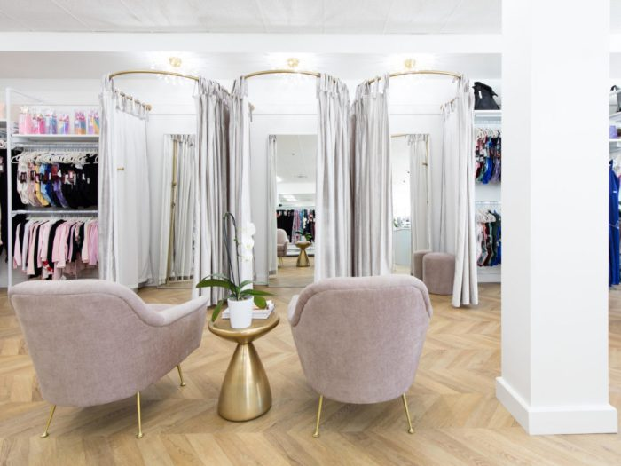 Two plush armchairs in off white, with three fitting rooms, with off white drapes on a circular rod.