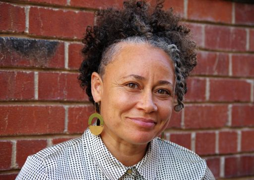 Cria Merchant, a Black woman with curtly hair, smiles softly at the camera, wearing a checked button-down shirt and large geometric earrings. A brick wall is behind her.