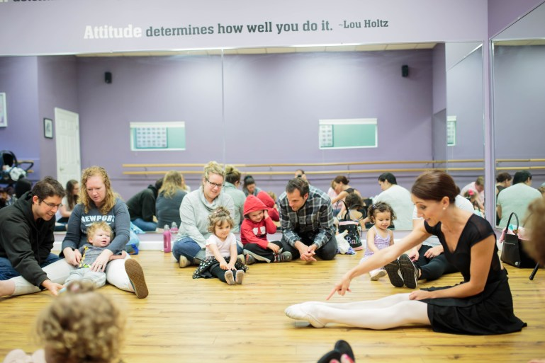 Nicole Ciotta sits on the floor, legs extended, pointing at her toes. Surrounding her are parents with their toddlers, who imitate her.