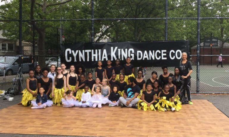 """Cynthia King and her students pose on an outdoor stage, with a """"Cynthia King Dance Co"""" banner behind them. The students wear black leotards with skirts made of caution tape."""