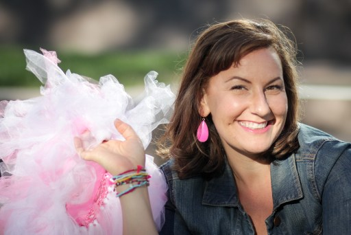 Katrena Cohea, a white woman with brown hair, smiles at the camera. holding a pink tutu in one hand. She is outside, and wears a jean jacket and pink earrings.