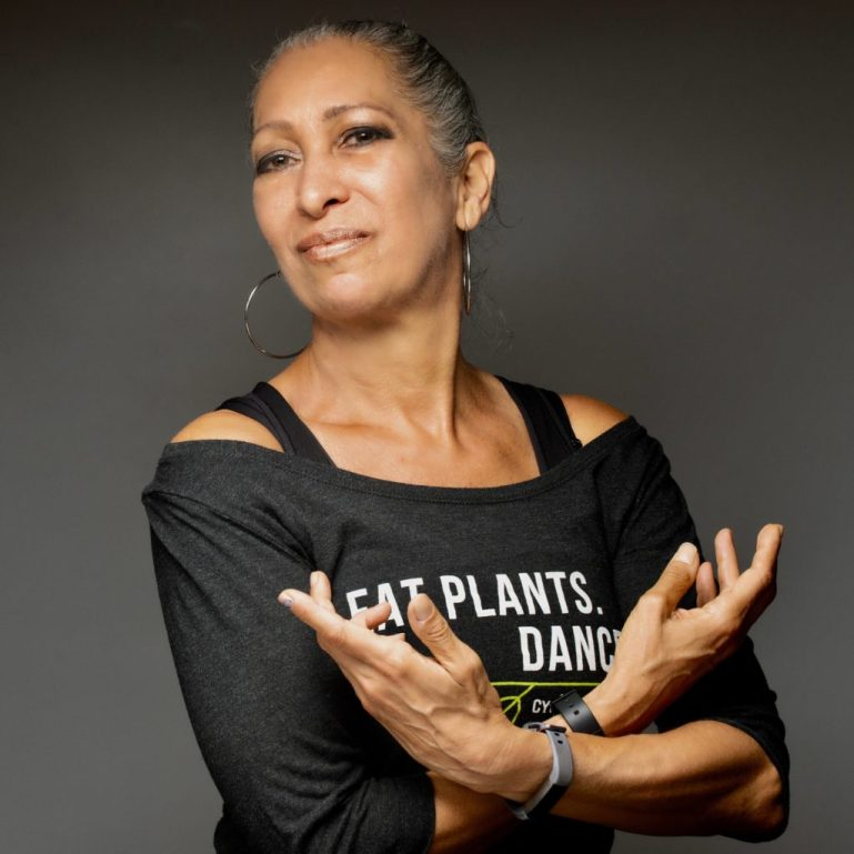"""Cynthia King, wearing a """"Eat Plants. Dance"""" shirt, crosses her arms, palms facing up with balletic hands. She is a Black woman with her hair pulled back, wearing large hoop earrings."""