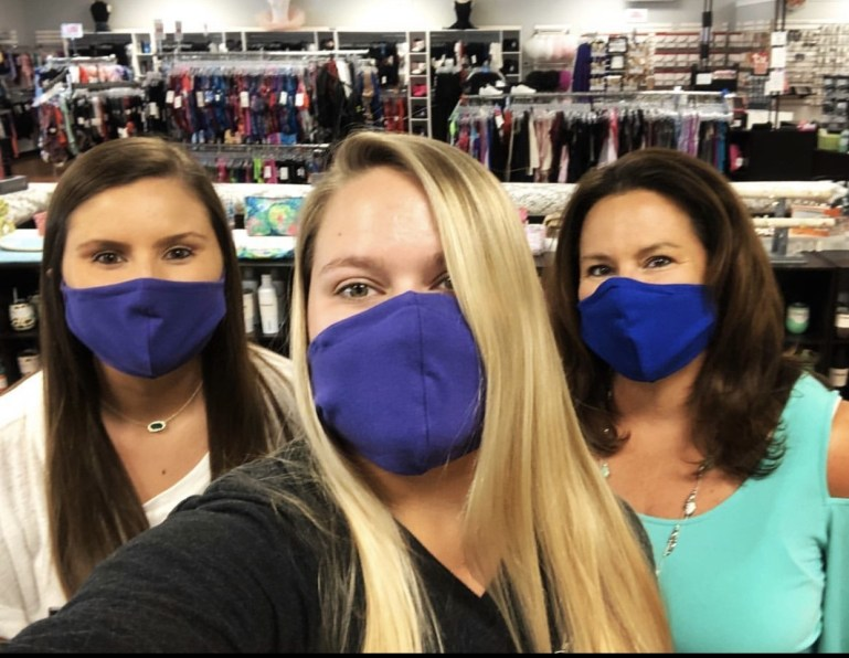Three women in masks working in a dance store.