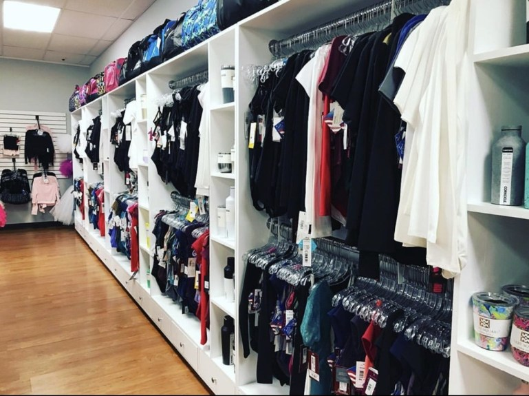 Racks of dance leotards along a wall, in white wall cabinet