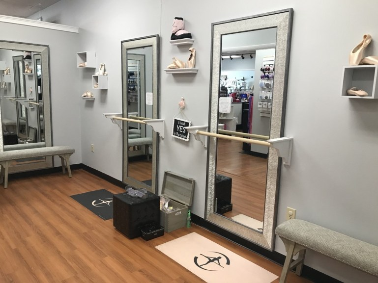 Two large mirrors with barres in front of them for pointe shoe fitting.