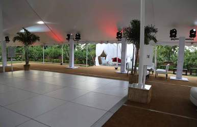 white dance floor under large tent with palm tree