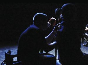 Dark and silhouetted image of a person seated in a wheelchair with their hands on an audience member's back. Audience member is seated on a stool. Both people are in profile and dressed in black. In the background is another pair in the same relationship.