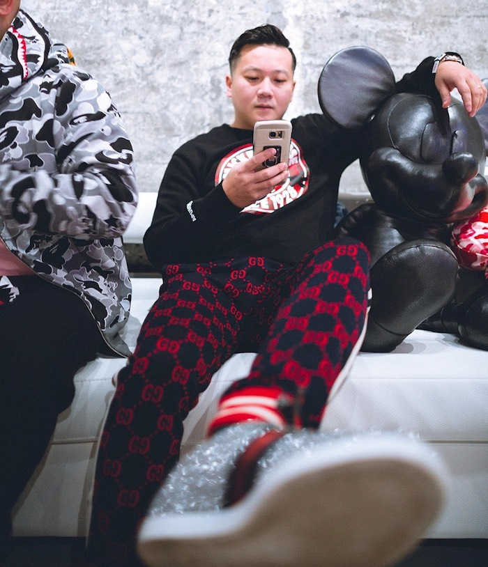 Chuck Wang in the Hypebeast Room at Vue, next to a leather Mickey Mouse