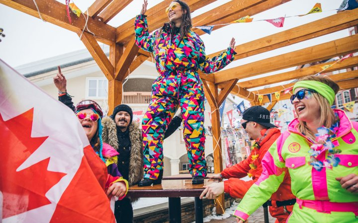 Canadians dancing in rainbow snow gear at Snowbombing