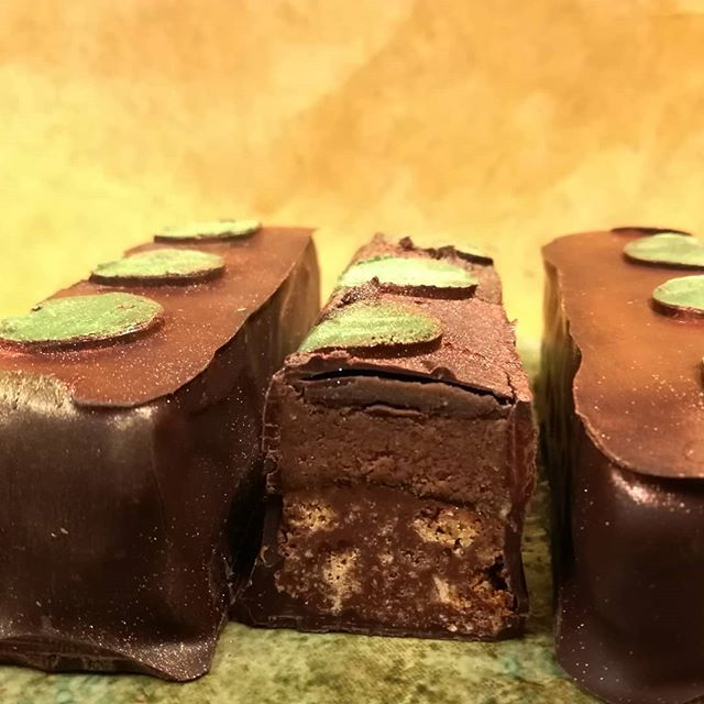 "CANDY BAR ""Somewhere Else"" - Thai Basil coconut ganache above caramel above chocolate chip cookie crunch.#chocolatier #chocolateasart #candybar @finechocolateindustryassoc"
