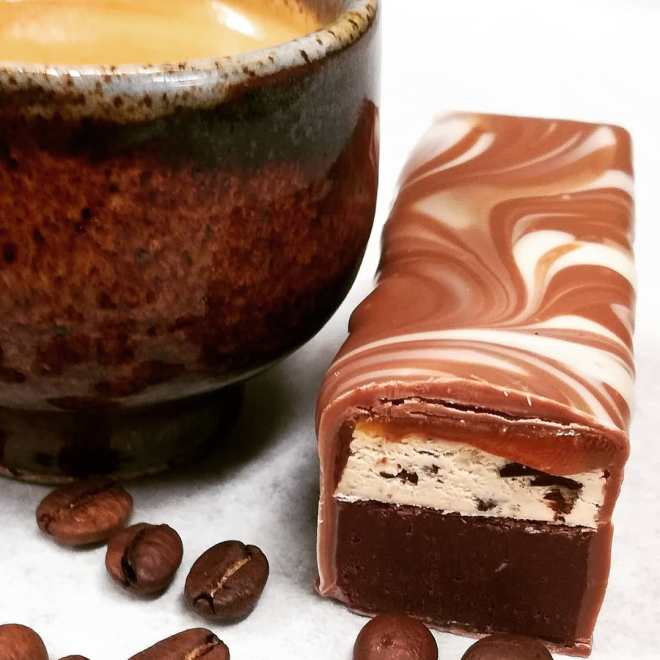 ESPRESSO BAR - espresso & housemade Sierra Leone dark chocolate ganache, espresso nougat, and butter caramel in Jivara and Ivoire. Contains barley malt.A fine way to begin a morning.#candybar #espresso #coffee @riverwalknashua @valrhonausa
