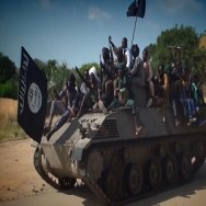 A screengrab taken on November 9, 2014 from a new Boko Haram video released by the Nigerian Islamist extremist group Boko Haram and obtained by AFP shows Boko Haram fighters parading on a tank in an unidentified town. The leader of the Nigerian Islamist extremist group Boko Haram, Abubakar Shekau, dismissed again government claims about ceasefire talks and threatened to kill the man who has presented himself as Boko HaramТs negotiator.  AFP PHOTO / HO / BOKO HARAM