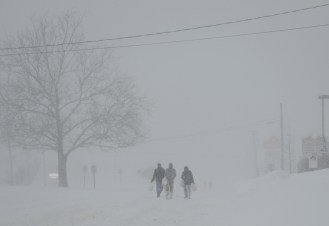Three pedestrians, outfitted with bags on their feet, brave the whiteout conditions on Saturday, January 23, 2016 to transport groceries along Route 40 in Catonsville, Md. Winter Storm Jonas dumped 29 inches of snow onto the Greater Baltimore area, which was a record for a single snowstorm. Photo by David Andrews.