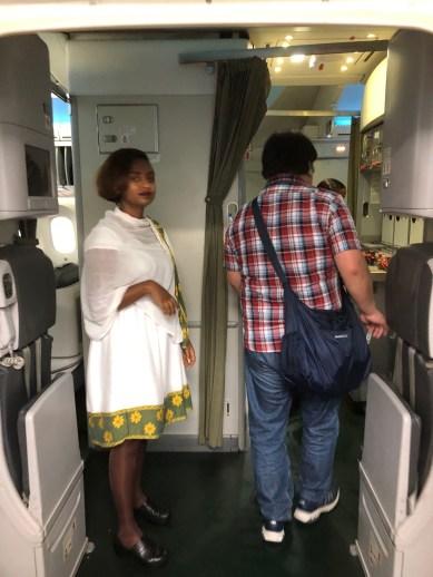 機内の入り口にて乗客を迎える伝統衣装を着たキャビンアテンダント