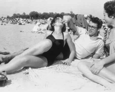 James Dean relaxing on the beach with his girlfriend Barbara Glenn