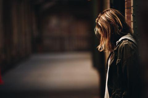 woman leaning against a wall in dim hallway